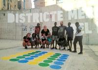 Joves dels centres oberts del Centre Històric pinten jocs tradicionals en una plaça del barri